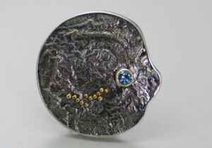 BRPN–3: Oxidized reticulated silver, 22k, 14k gold, blue topaz. Brooch may be worn as a pendant. 1.75 inches. SOLD
