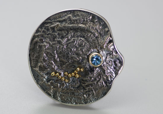 BRPN-3-Oxidized reticulated silver, 22k, 14k gold, blue topaz. Brooch may be worn as a pendant. 1.75 inches.