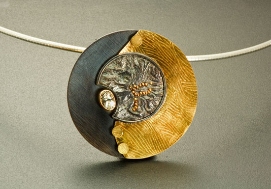 NKL–3: Oxidized reticulated silver, 22k, 18k gold on silver, tourmaline. Pendant 1.75 inches by 1.75 inches. 16 inch omega chain included. 18 inch chain available for an additional cost per market.