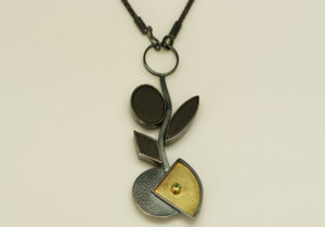 NKL–4: Oxidized silver, 18k gold on silver, 14k gold, peridot black onyx, 18 inch chain, pendant 3.50 inches by 1.50 inches.
