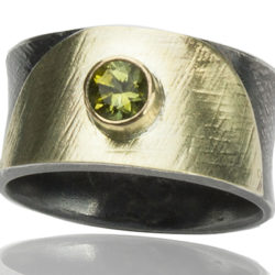 "R–18: Peridot 5mm set in 18k gold, with 22k gold on oxidized sterling silver.Size 7.25. $500.00 [add_to_cart id=""765""]"