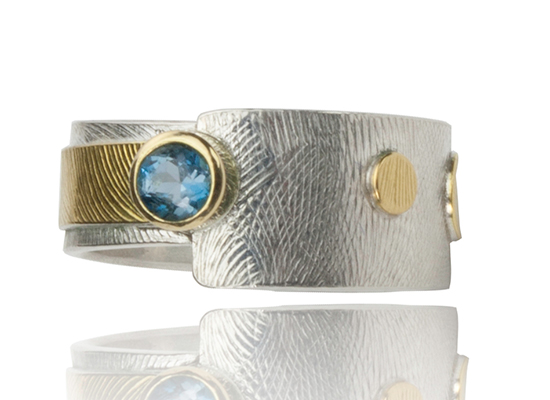 R–23: Sterling silver, 22,18k gold blue topaz, 18,22k gold. Size 7.75. Sold